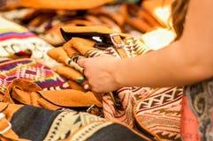 OTAVALO, ЭКВАДОР - 17-ОЕ МАЯ 2017: Закройте вверх красивой усмехаясь одежды молодой женщины касающей андийской традиционной Стоковое фото RF
