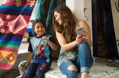 OTAVALO, ЭКВАДОР - 17-ОЕ МАЯ 2017: Красивая молодая женщина держа ее мобильный телефон с ее рукой и разговаривая с Стоковое Изображение RF