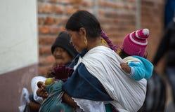 Indigenous quechua woman carrying toddler on her back in Ecuador. Otavalo, Ecuador - December 30, 2017: indigenous quechua woman carrying child on her back  in Stock Image