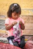People in Ecuador. OTAVALO, ECUADOR - JAN 3, 2015: Unidentified Ecuadorian little girl with onion at the Otavalo Market. 71,9% of Ecuadorian people belong to the royalty free stock photo