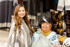 OTAVALO, ECUADOR - MAY 17, 2017: An unidentified hispanic indigenous woman wearing andean traditional clothing and. Necklace, with a beautiful caucasian woman royalty free stock photo