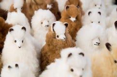 OTAVALO, ECUADOR - MEI 17, 2017: Het mooie Andes kleine lamastuk speelgoed textielgaren en langs geweven dient wol, in wit in Royalty-vrije Stock Afbeeldingen