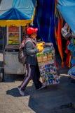 OTAVALO, ECUADOR, 06 NOVEMBER, 2018: Niet geïdentificeerde mensen verkopende producten in de straat dicht bij straatmarkt met typ stock foto
