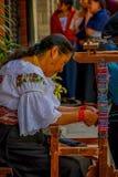 OTAVALO ECUADOR, NOVEMBER 06, 2018: Oidentifierad kvinna som arbetar i ett handgjort armband i trottoaren på staden av arkivbild