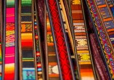 OTAVALO, EQUADOR - 17 DE MAIO DE 2017: Fio de matéria têxtil tradicional andino bonito da correia e tecido à mão nas lãs, colorid Fotografia de Stock