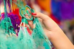 OTAVALO, EQUATEUR - 17 MAI 2017 : Fermez-vous d'une femme tenant un catchdreamer magenta dans sa main, sur le marché coloré Photo stock