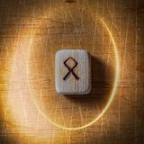 Othala. Handmade scandinavian wooden runes on a wooden vintage background in a circle of light. Concept of fortune stock photos