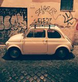 An other night in Roma. A little car in front of graffitis in a small street if Roma Stock Photography