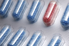 The other pill. Blue pills in a package with a red one in between Royalty Free Stock Image