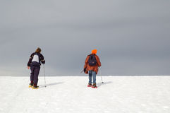On the other side. Snowshoes trekking under grey sky Stock Photography