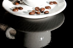 On the other side. Reflection of a coffee cup with coffee beans on the plate Royalty Free Stock Photo