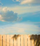 Other Side of the Fence. View over a fence toward a bright blue sky Stock Photo