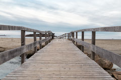 The Other Side. A wooden beach crossing a little river in the beach Royalty Free Stock Image