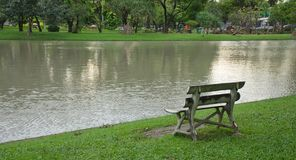 An other view of A wooden chair that placing alongside the lake created a distraught scenic under the light of the evening, giving. A classic scene of the park Royalty Free Stock Photo
