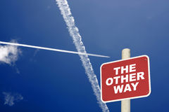 The other way sign with jet trails crossing a blue sky Royalty Free Stock Photography