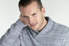 Otitis - молодой человек с инфекцией уха стоковая фотография
