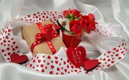 Otkrtyka rojo y blanco con los corazones, un cubo de rosas, un regalo y cintas Fotografía de archivo
