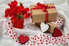 Otkrtyka rojo y blanco con los corazones, un cubo de rosas, un regalo y cintas Foto de archivo libre de regalías
