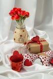 Otkrtyka rojo y blanco con los corazones, un florero con las rosas, un regalo y cintas para el día del ` s de la tarjeta del día  Fotos de archivo libres de regalías