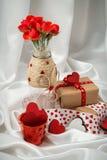 Otkrtyka rojo y blanco con los corazones, un florero con las rosas, un regalo y cintas para el día del ` s de la tarjeta del día  Imagenes de archivo