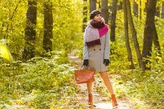Otoño, estación y concepto de la gente - mujer en capa con el bolso marrón que se coloca en parque del otoño imágenes de archivo libres de regalías