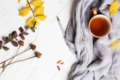 Otoño flatlay en el contexto de madera con una taza de té y caida Imagen de archivo