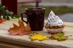 Otoño, hojas de arce, taza, té, cesta de la torta Foto de archivo