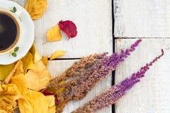 Otoño, hojas de la caída, taza de café de cocido al vapor al vapor caliente y flores en fondo de madera de la tabla Estacional, e Imágenes de archivo libres de regalías
