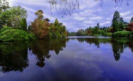 Otoño inglés con el lago, los árboles y el sol visible irradia - Uckfield, Sussex del este, Reino Unido imagenes de archivo