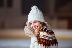 Otoño, retrato del invierno: La mujer sonriente joven se vistió en una rebeca de lana caliente, los guantes y el sombrero present Imagen de archivo libre de regalías