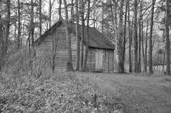 Otoño, un edificio de madera en el bosque, imagen blanco y negro foto de archivo