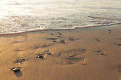Otoczaków kamienie na plażowym piasku, wschód słońca obraz royalty free