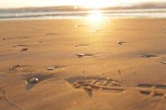 Otoczaków kroki na piasku przy wschodem słońca i kamienie fotografia royalty free