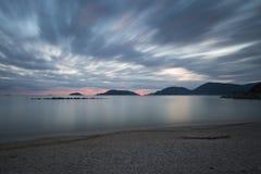 Otoczak plaża przy zmierzchem z chodzenie chmurami i silky morzem fotografia stock