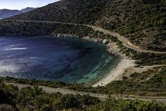 Otoczak plaża w małej zatoce z kryształem - jasny błękitny nawadnia pod jasnymi niebieskimi niebami Zdjęcie Royalty Free