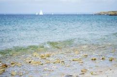 Otoczak plaża z błękitnym morzem i białą łodzią w tle, Fotografia Royalty Free