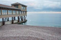 Otoczak plaża z domem na molu przy zmierzchem Zdjęcia Stock