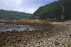 Otoczaka kamienia plaża z niebieskim niebem Fotografia Stock