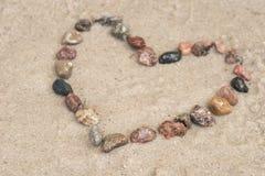 Otoczaka kierowy kształt na piasku Obraz Royalty Free