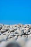 Otoczaka niebieskie niebo na tle i plaża Obrazy Stock
