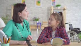 Otolaryngologist доктора помогает положить дальше слуховой аппарат к слуху - поврежденный девочка-подросток акции видеоматериалы
