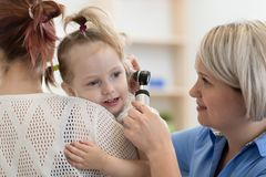 Otolaryngologist do ` s da criança que faz o exame de orelha da menina imagens de stock