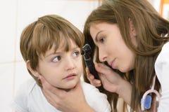 Otolaryngologist examining a kid ear Stock Photo