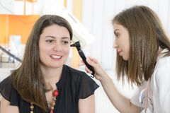Otolaryngologist examining a woman ear Royalty Free Stock Photos