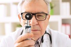 Otolaryngologist looking through otoscope Stock Image
