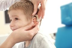 Otolaryngologist putting hearing aid in little boy's ear indoors royalty free stock photo