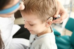 Otolaryngologist putting hearing aid in little boy's ear indoors royalty free stock images