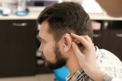 Otolaryngologist putting hearing aid in man's ear in hospital stock photography