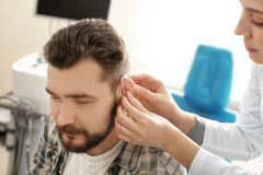 Otolaryngologist putting hearing aid in man's ear in hospital stock photos