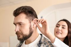 Otolaryngologist putting hearing aid in man's ear on light background royalty free stock photography